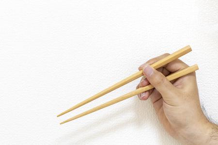 Male hand holding a wooden chopsticks