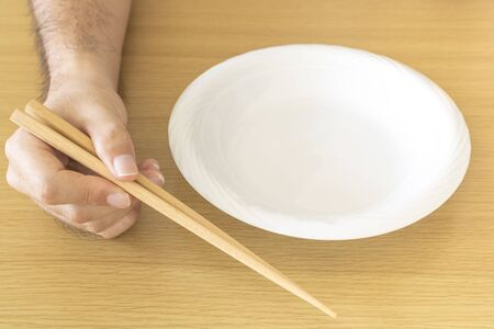 Male hand and white dish with chopsticks