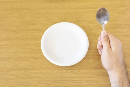 Male hand waiting for meal holding spoon