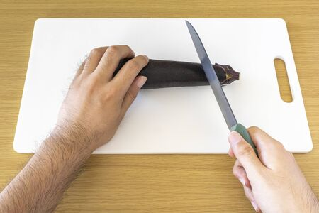 Image of man using chopping board and knife