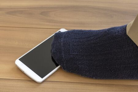 Feet of a man stepping on a dropped smartphone
