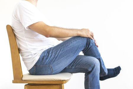 Man sitting on chair and crossing legs