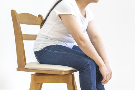 A little fat woman sitting in a chair and being weak