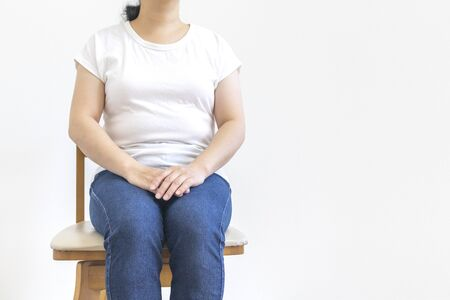 A little fat woman sitting in a wooden chair Stock Photo