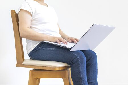 A little fat woman sitting on a chair and using a laptop