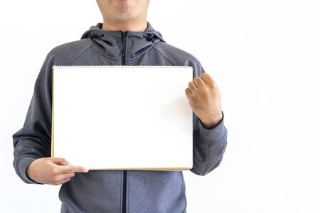 A man in a gray jersey holding a sketchbook