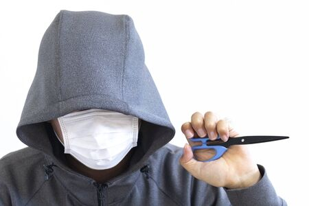 Suspicious man with scissors and hiding his face