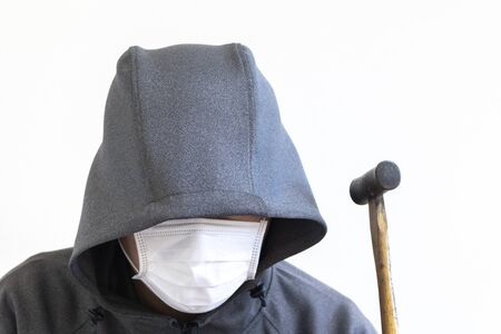 Suspicious man holding a hammer and hiding his face