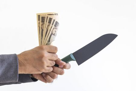 Male hand holding a kitchen knife and banknotes
