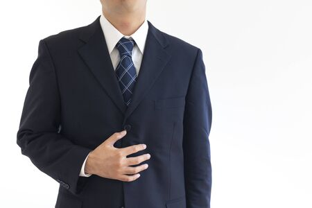 A man in a suit suffering from holding his stomach