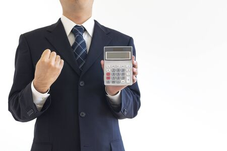 A man in a suit holding a calculator
