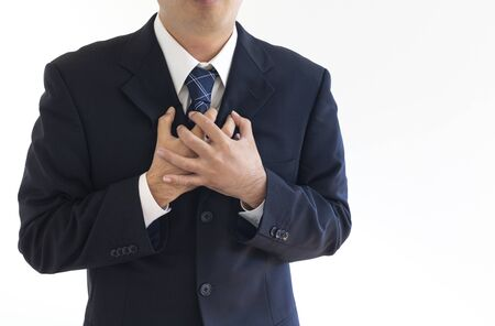 A man in a suit holding his chest and suffering