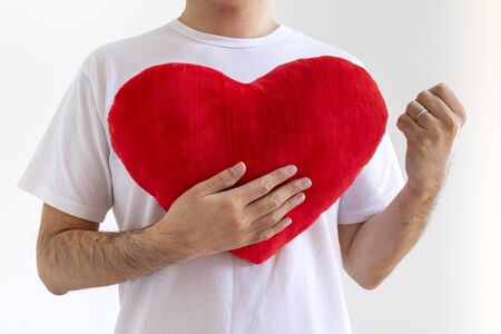 A man wearing a white shirt fisted with a heart cushion