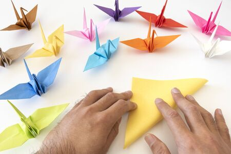Hand of a man folding a crane with origami