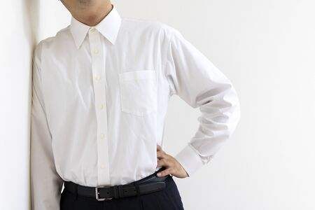 A man wearing a business shirt resting leaning against a wall