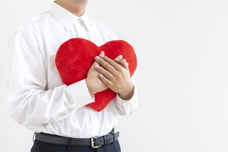 A man wearing a business shirt with a heart cushion