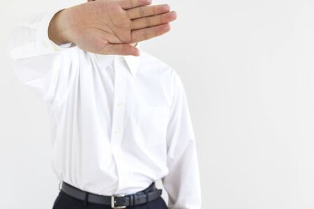 A man wearing a business shirt hiding his face with his hands