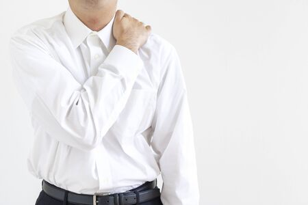 A man in a business shirt holding his shoulder