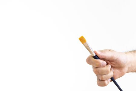 Man's hand holding a paint brush