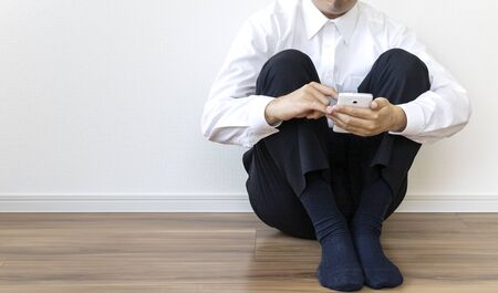 A man in a business shirt sitting on the floor and operating a smartphone