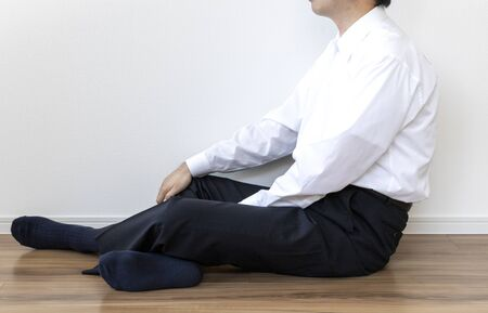 Man in business shirt sitting on the floor and resting Stock Photo