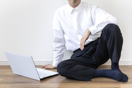 A man in a business shirt sitting on the floor and operating a laptop