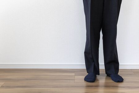 Lower body of a man wearing suit pants