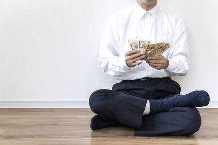 A man in a business shirt sitting on the floor and counting bills