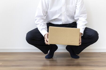Man in business shirt sitting on the floor with cardboard