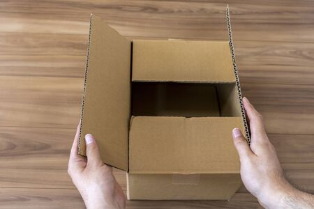 Men's hand opening a cardboard box
