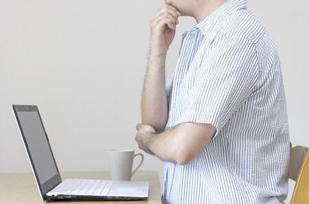 A man at home working on a laptop in plain closure and thinking. Image of Working from Home and Side Business