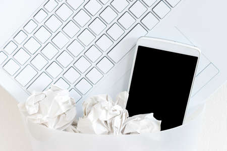 Laptops and smartphones thrown in the trash. Image of digital detox