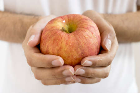 Close-up of an apple in a man's hand