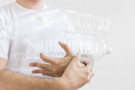 Man holding a lot of empty plastic bottles