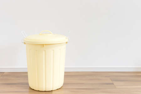 A yellow 45-liter trash can placed indoors
