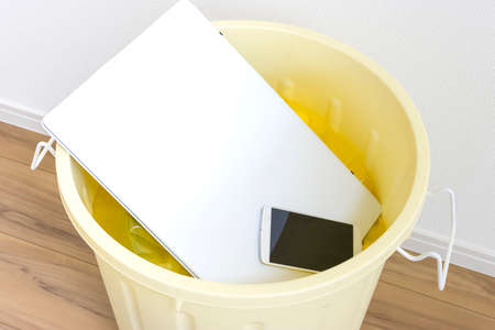 Laptops and smartphones thrown away in a poly bucket. Image of digital detox