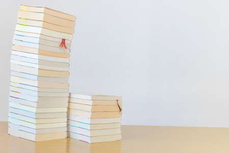 Many books stacked on the desk