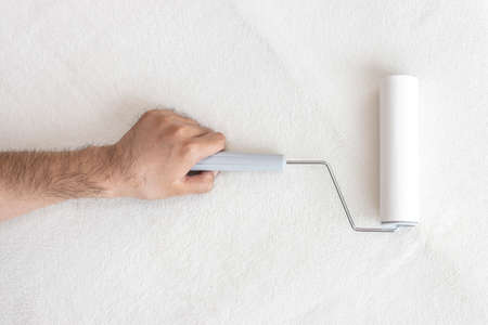 A man's hand cleaning a white carpet with a lint roller