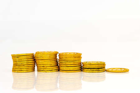 Declining gold coin graph, white background, business image, declining image Stock Photo