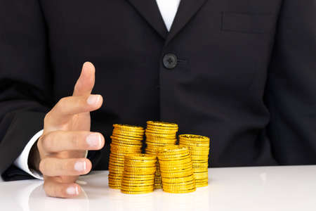 Stacked gold coins and men's hands in suits, business image, financial image