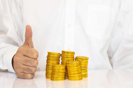 Stacked gold coins and men's hands in business shirt, business image, financial image
