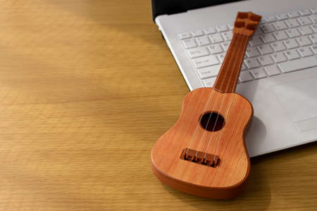 Image of practicing by looking at a computer. Laptop and toy guitar