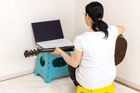 Image of a woman practicing guitar while looking at a computer