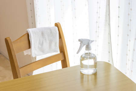 Towel and alcohol spray. Image of disinfecting the table with alcohol