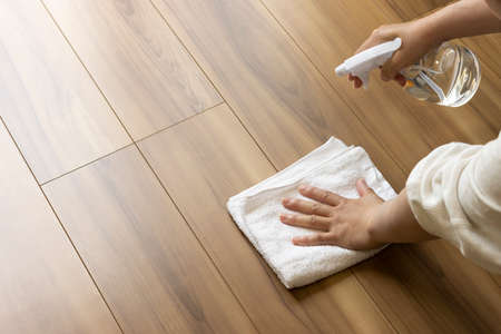 Towels and alcohol spray and women. Image of disinfecting the floor with alcohol