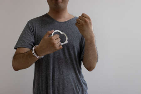 A man (30's, Japanese) who removed his handcuffs. Image of jailbreak Stock Photo