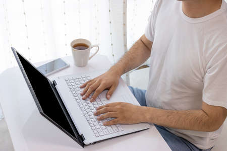Image of a man working on a computer at a table at home (young, 30s, Japanese) Stock Photo