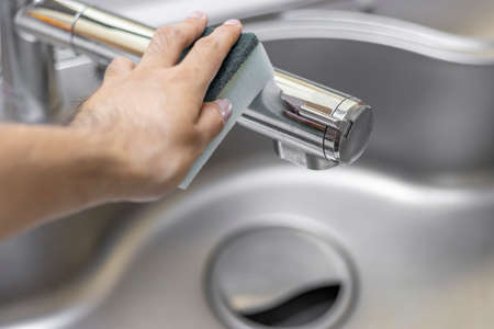 Image of a man's hand cleaning a kitchen faucet