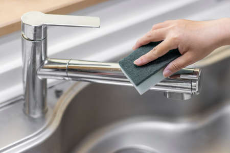 Image of a woman's hand cleaning a kitchen faucet
