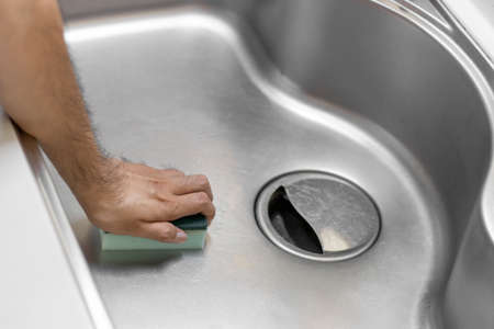 Image of a man's hand cleaning a kitchen sink